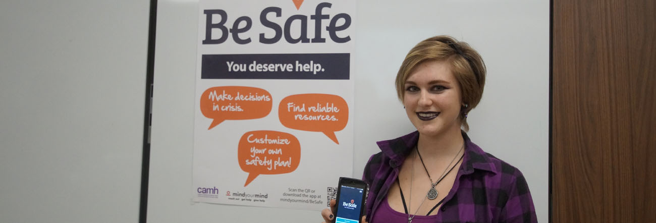 Female student holding cell phone with Be Safe App and Be Safe poster in background